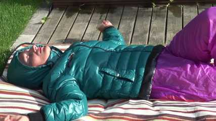 Watching Sandra taking a sun bath and watering the garden the pest plants wearing a sexy purple rain pants and a green down jacket (Video)