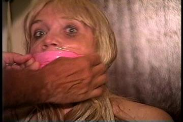 50 Yr OLD REAL ESTATE AGENT IS NUDE, TIT TIED, CROTCH ROPED, WRAP BONDAGE TAPE GAGGED, CLEAR TAPE GAGGED AND  HANDGAGGED WHILE TIED TO A CHAIR (D71-15)