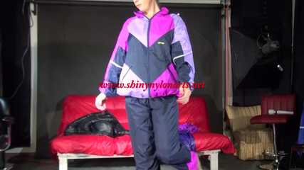 Watching Pia wearing a blue/purple/pink shiny nylon rain suit folding clothes and tidying up the studio (Video)