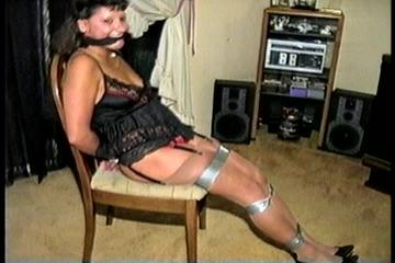33 YEAR OLD AMERICAN INDIAN TRISH IS HANDCUFFED, MOUTH STUFFED, CLEAVE GAGGED, CHAIR TIED, BALL-GAGGED, HANDGAGGED WEARING LINGERIE, GARTER BELT, NYLONS & HEELS (D70-10)
