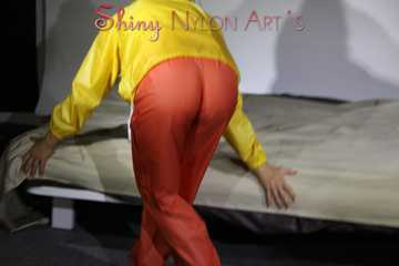 Watching Sandra wearing supersexy shiny nylon rainwear in yellow and orange preparing her bed and lolling in it with this shiny rainwear (Pics)