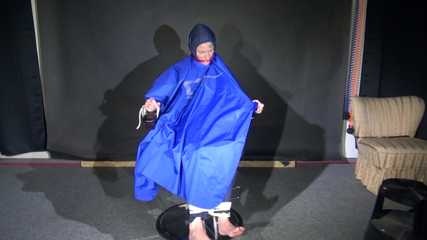 Watching Sonja sitting on a hairdresser`s chair wearing sexy blue shiny nylon rainwear with a raincape being tied, gagged and hooded with ropes and a clothgag (Video)